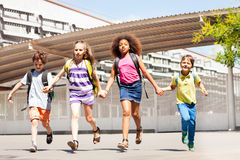 Excited kids run, hold hands near school building Stock Photos