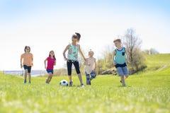 Boys and girls running towards football. Boys and girls running towards ball on a field Stock Photo