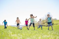 Boys and girls running towards football. Boys and girls running towards ball on a field Stock Images
