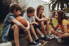 Group of kids sitting together and talking. Boys and girls sitting on the pavement and talking. Girl sitting down on the edge of a street showing her mobile stock image