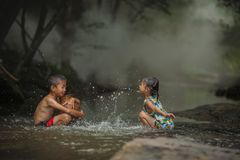 Boys and girls smiling and happiness playing water at countrysid stock image
