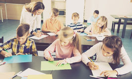 Boys and girls with teacher drawing. Little boys and girls with teacher drawing in classroom Royalty Free Stock Photo