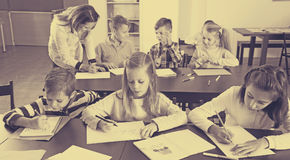 Boys and girls with teacher drawing. Portrait of pretty little boys and girls with teacher drawing in classroom Stock Images
