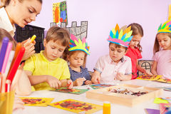 Boys, girls and teacher glue paper to cardboard Royalty Free Stock Image
