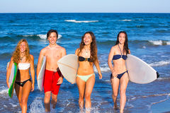 Boys and girls teen surfers coming out from the beach Royalty Free Stock Photos