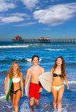 Boys and girls teen surfers coming out from the beach Stock Photography