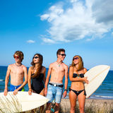 Boys and girls teen surfers happy smiling on beach. Boys and girls teen surfers happy smiling over dune beach in summer Royalty Free Stock Photo
