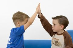 Boys giving five. Young boys giving five. Focus on the face Stock Image