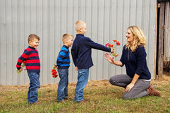 Boys giving flowers to Mum Stock Photography