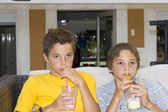 Boys with glasses of milkshake Stock Images