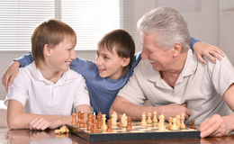Boys and grandfather playing chess Royalty Free Stock Image