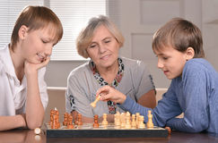Boys and grandmother playing chess Royalty Free Stock Images
