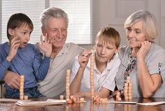 Boys and grandparents playing lotto. Portrait of two boys and grandparents playing lotto at home Stock Images