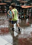 Boys playing in the rain next to empty tables during rain storm in St. Louise at Grand Farm. These boys had to run out in the rain and splash around. This food Royalty Free Stock Image
