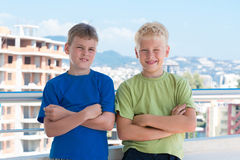 Boys with hands on chest are on background of building. Two smiling boys with hands on chest in colored T-shirts are on the background of building under royalty free stock image