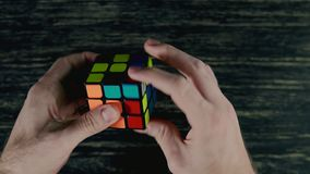 Boys hands solving puzzle cube at dark background. Top view in 4k, UHD, close up stock footage