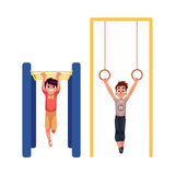 Boys hanging on gymnastic rings and monkey bars at playground Royalty Free Stock Photography