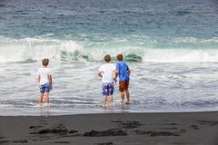 Boys have fun at the black beach Royalty Free Stock Photos