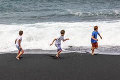 Boys have fun at the black   beach Stock Photos