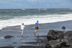 Boys have fun at the black volcanic beach Royalty Free Stock Photo