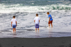 Boys have fun at the black volcanic beach Royalty Free Stock Photos