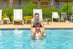 Boys have fun playing piggyback in the pool Royalty Free Stock Images