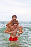 Boys having fun in the beautiful clear sea. By playing pickaback Stock Photography