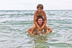 Boys having fun in the beautiful clear sea Royalty Free Stock Photos
