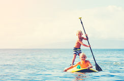 Boys Having Fun Stand Up Paddling Royalty Free Stock Photography