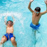 Boys having great time in pool. Portrait of two boys splashing water together in pool Royalty Free Stock Photos
