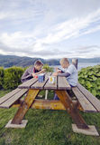 Boys having picnic meal. Two boys sitting at a wooden picnic table and eating. Fjord scenic in the background, Norway summer holidays Royalty Free Stock Photography