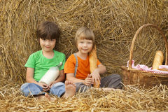 Boys on a haystack with bread and milk Stock Photo