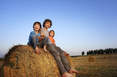3 boys in a haystack in the field Stock Photos