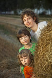 3 boys in a haystack in the field Stock Image