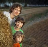 3 boys in a haystack in the field. In summer day royalty free stock image