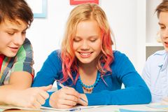 Boys help cute blond teen girl do homework Royalty Free Stock Photo