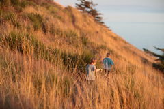 Boys Hiking On A Hill Next To The Ocean Royalty Free Stock Photos