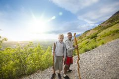 Boys Hiking up a beautiful mountain trail in the summer Stock Photo