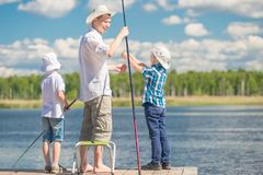 Boys with his father on the pier while fishing. Holding a weekend concept royalty free stock images