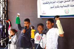 Boys holding puppets stuffed dolls and acting a play on stage. With microphones in front of them wearing tee shirts at charity event related USAID, at a camp Stock Image
