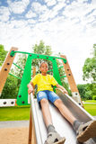 Boys holds sides of chute and sits on it Royalty Free Stock Images