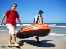 Boys on holidays. Two young men walking along beach with rubber boat Stock Image