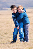Boys hugging. Eachother and smiling Royalty Free Stock Image
