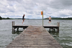 Boys jumping into the lake Royalty Free Stock Image