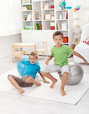 Boys jumping on large gymnastic balls and falling Stock Photography