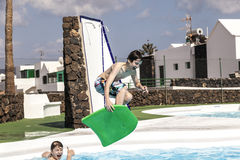Boys jumping in the pool. With the surfboard Royalty Free Stock Photos