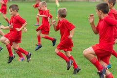 Boys kicking ball Stock Images
