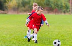 Boys kicking ball. Boys kicking football on the sports field royalty free stock photography