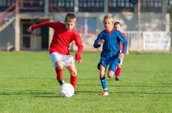 Boys kicking ball Stock Photography