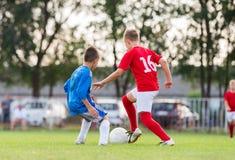 Boys kicking ball Stock Photos